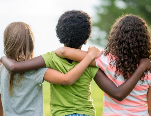 Kinder verschiedener Herkunft halten sich im Arm